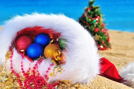 Christmas baubles and gift boxes in the christmas hat against blue ocean photo