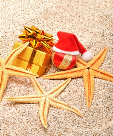 Starfishes, christmas bauble and a gift box on the sand photo