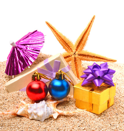 Starfish, christmas baubles, gift boxes on the sand isolated on white photo