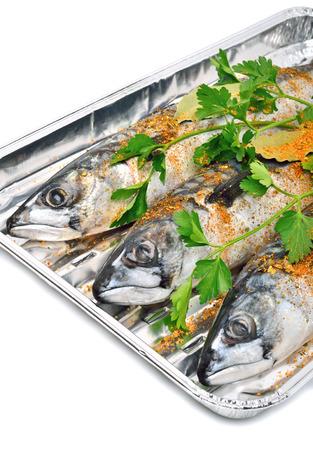 homeware: Fresh mackerel fish with parsley on the aluminium foil tray isolated on white Stock Photo