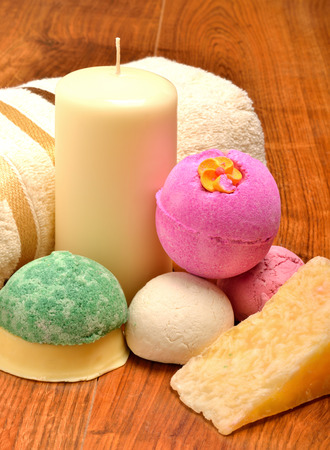 Candle, soap, bath bombs and bath towel on the wooden background