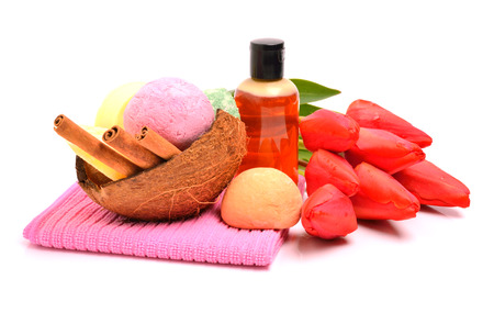 Soap, bath bombs, gel, cinnamon sticks in the coconut shell and tulips isolated on white photo