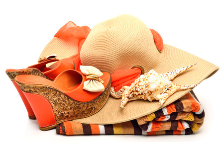 Beach hat, towel, stylish woman shoes and a seashell isolated on white