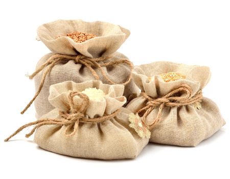 Rice, barley and buckwheat in cloth sacks isolated on white photo