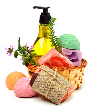 Different handmade soaps, bath bombs, gel and herbs in the basket isolated on white