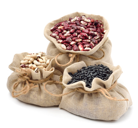 red kidney beans, black beans and black-eyed beans in the sacks isolated on white photo