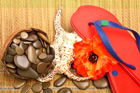 seashell, flower, pebbles and flip flop sandals on the tablecloth photo
