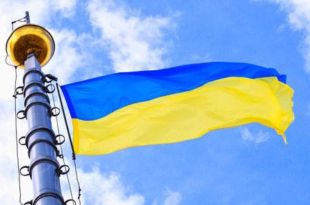 Ukrainian flag blowing in the wind against the blue sky photo