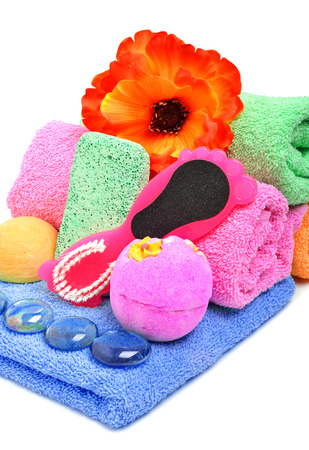 Bath towels, pumice, glass pebble and flower isolated on white photo
