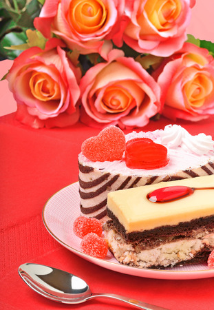 Valentines cakes, tarts and red roses on the red tablecloth photo