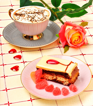 Cup of coffee, a rose and a cake on the tablecloth photo