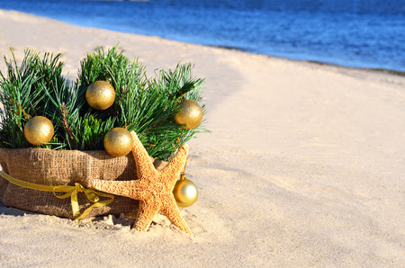 beach wrap: Christmas tree with golden christmas balls and starfish on the sand on the beach Stock Photo