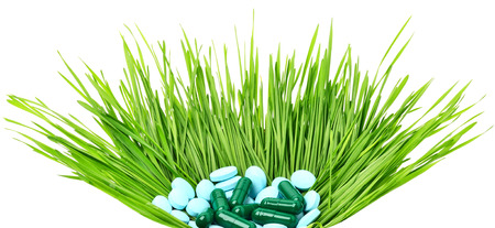 herbology: Pills, tablets and wheat grass in the basket on white