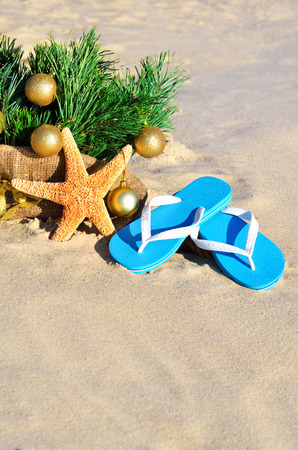 Christmas tree with christmas balls, slippers and starfish on the sand on beach