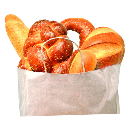 Fresh bread in the paper bag isolated on white photo