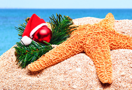 Starfish, christmas baubles and pine twig on the sand isolated on white photo