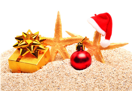 Starfishes, christmas bauble and a gift box on the sand isolated on white photo