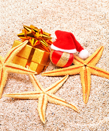 christmas hat, starfishes, christmas bauble and a gift box on the sand photo