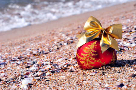 Red christmas bauble with golden bow on the sand against blue ocean Stock Photo