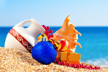 antique vase: Antique vase, christmas baubles, gift box and seashell on the sand against blue ocean