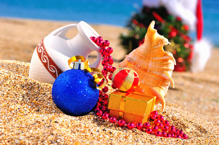 antique vase: Christmas tree, antique vase, christmas baubles, gift box on the sand against blue ocean