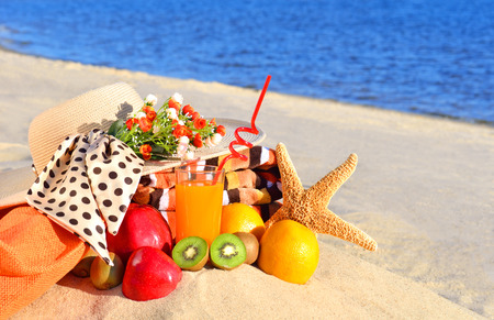Woman hat, different fruits, starfish and  glass of juice on the sand on the beach photo