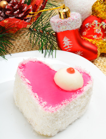 Christmas delicious heart shaped cake with coconut chips on christmas background photo