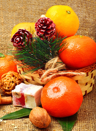 Christmas tangerines with sweet delights, walnuts, pinecone and brittle candies on christmas sacking background photo