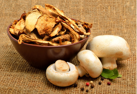 bawl: Dried mushrooms in the bawl, ceps and raw champignons on the sacking background