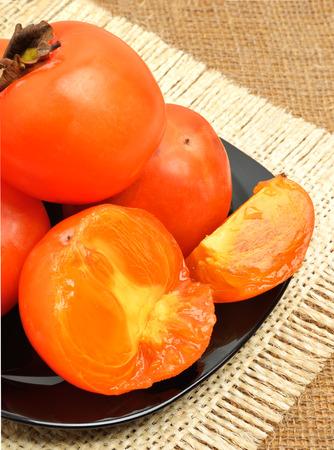 sacking: Sweet ripe persimmon fruits on black plate on sacking background