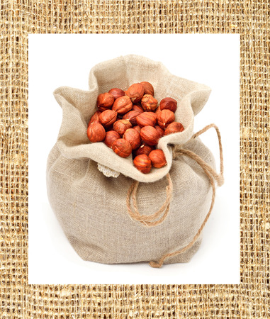 Hazelnut in the sack bag isolated on white. Frame made of sacking. Collage photo