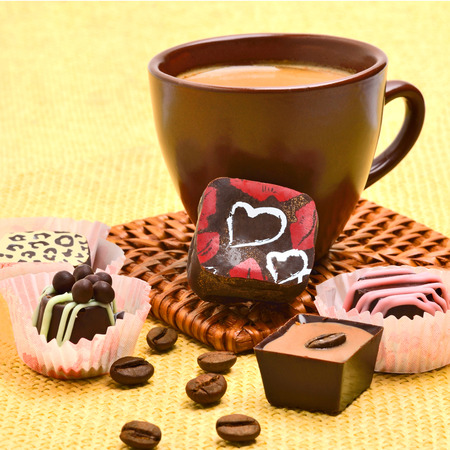 cafe bombon: Taza de caf� con dulces de chocolate y granos de caf� en el mantel Foto de archivo