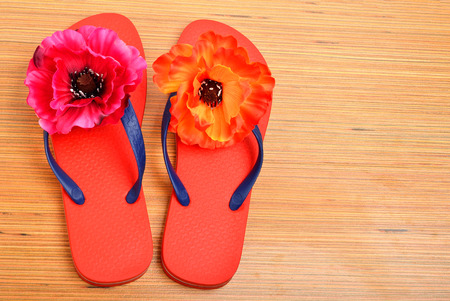 Red flip-flops, slippers with flowers on the wooden background photo