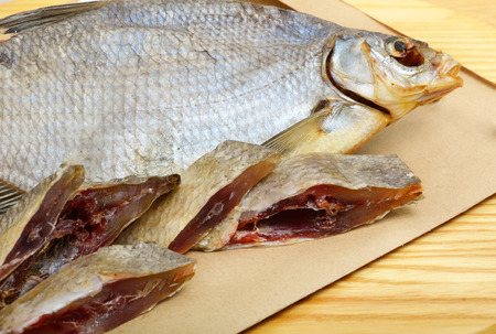marinelife: Bream on paper, on the wooden background. Pieces of fish Stock Photo