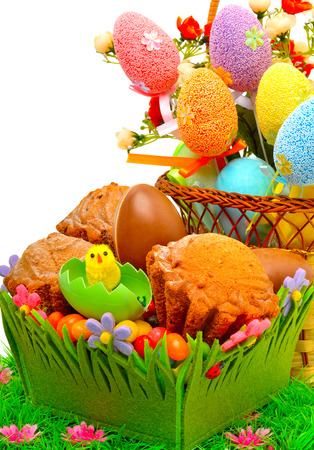 Easter eggs in the basket, chocolate eggs and muffins on the grass isolated on white photo