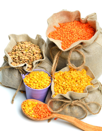 green, red and yellow lentils in the sacks and spoon wooden isolated on white background