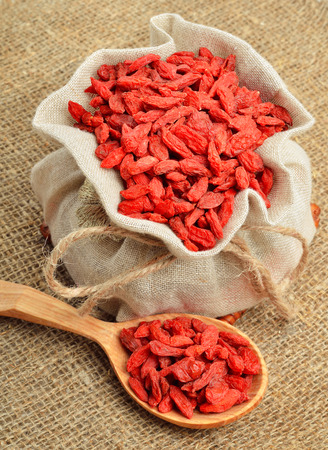 lycium: Goji berries in the sacking on a wooden background. Vitamin c fruit.