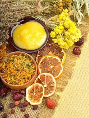 wild oats: Сalendula flower, oats, immortelle flower, tansy herb, honey, wild rose, dried lemon on sacking background