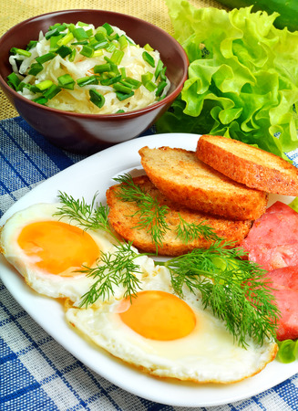 english breakfast: English breakfast, scrambled eggs with toasts, bacon, ham and vegetamles. Salad with cabbage, cucumber.