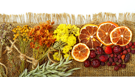 Calendula flower, oats, immortelle flower, tansy herb, honey, wild rose, dried lemon on sacking background photo