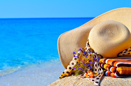 Woman beach hat, bright towel and flowers against blue ocean background photo