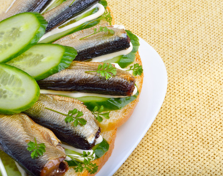 sprats: Sandwich with sprats and green cucumber on a plate