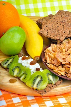 comiendo pan: La alimentaci�n saludable. La fruta fresca, cereales y panes secos con cuajada en un fondo de madera Foto de archivo