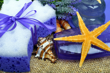 Spa concept, lavender flowers with liquid soap, bathroom accessories, starfish, on sacking background.