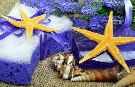 liquid soap: Spa concept, lavender flowers with liquid soap, bathroom accessories, starfish, on sacking background.