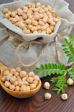 Chickpeas in a burlap bag on a wooden background