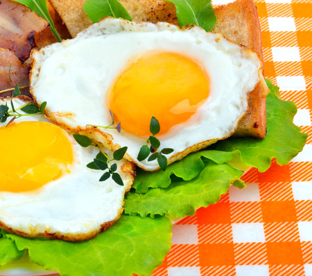 sunny side up: Bacon with sunny side up eggs served with toasts on a orange napkin Stock Photo