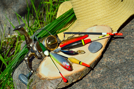 tackle: fishing tackle and hat against the backdrop of the stone