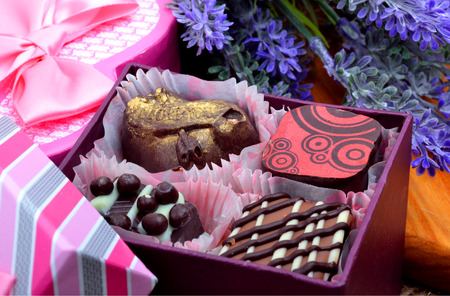 Assortment of chocolate sweets in gift boxes, lavender photo