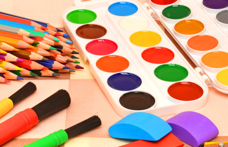 sharpeners: Paintbrushes, pencils sharpeners, colored pencils, water-colour paint on tablecloth